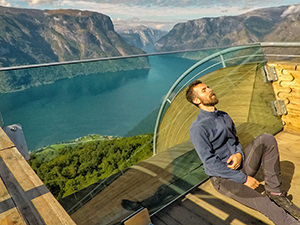 Pipeaway blogger Ivan Kralj resting his head and back on the angled glass pane at the end of the Stegastein lookout in Aurland, Norway, photo by Ivan Kralj
