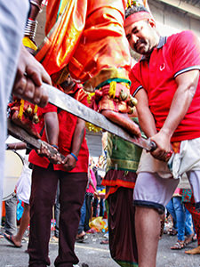 Devotee at Thaipusam Festival 2019 standing barefoot on sabers held in the air by fellow pilgrims, photo by Ivan Kralj