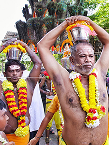 Friends Kumar and Govindarajoo, with pierced tongue and cheek, and paal kudam - milk pots on their head, walking in a procession to Batu Caves at Thaipusam Festival 2019, photo by Ivan Kralj