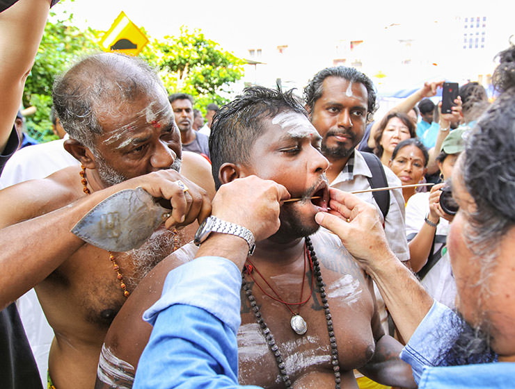 Piercing the cheeks of a devotee with a rod at Thaipusam Festival 2019 at Batu Caves, photo by Ivan Kralj