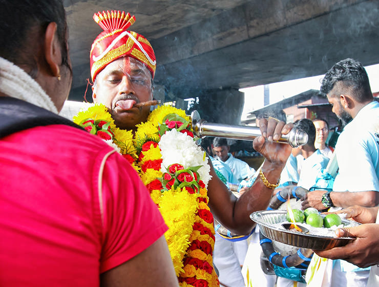 Devotee sticking out his tongue while smoking a cigar at Thaipusam Festival 2019 at Batu Caves, Malaysia, photo by Ivan Kralj