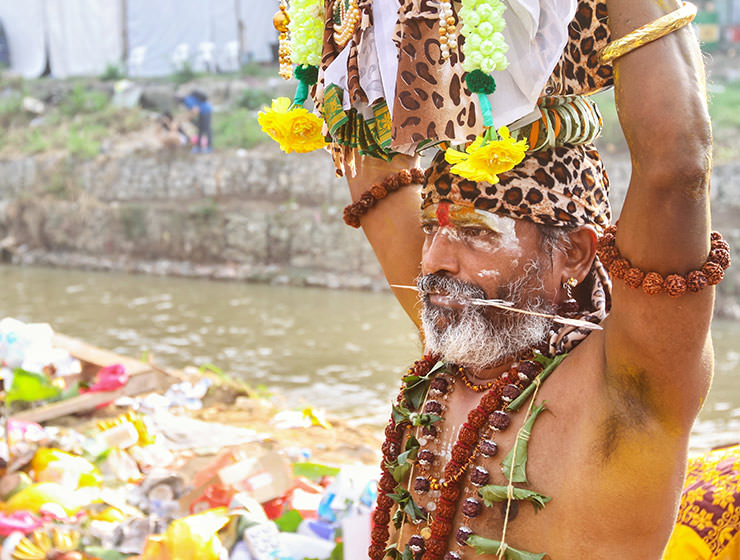 An oldr bearded devotee with pierced cheeks and tongue, carrying a paal kudam at Thaipusam Festival 2019 at Batu Caves, Malaysia, photo by Ivan Kralj