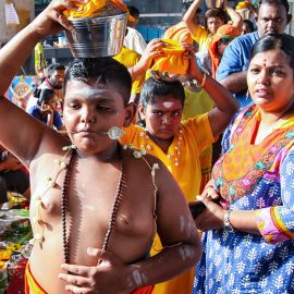 Young boy devotee with pierced tongue, carrying a paal kudam with his family at Thaipusam Festival 2019 at Batu Caves, Malaysia, photo by Ivan Kralj