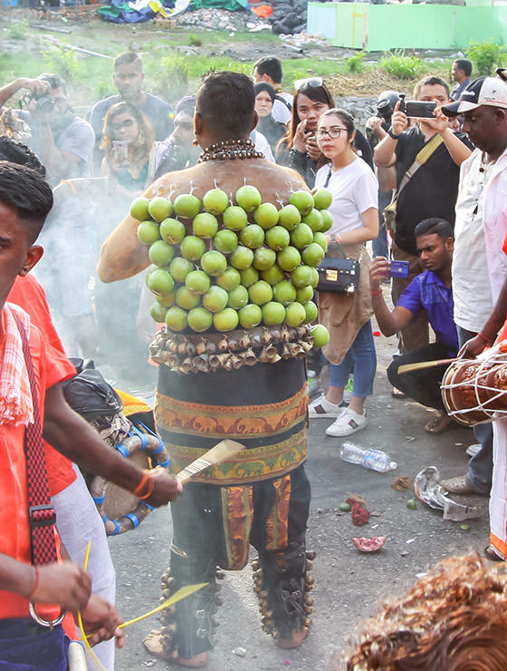 Devotee with dozens of green apples pierced on his back skin at Thaipusam Festival 2019 at Batu Caves, Malaysia, photo by Ivan Kralj