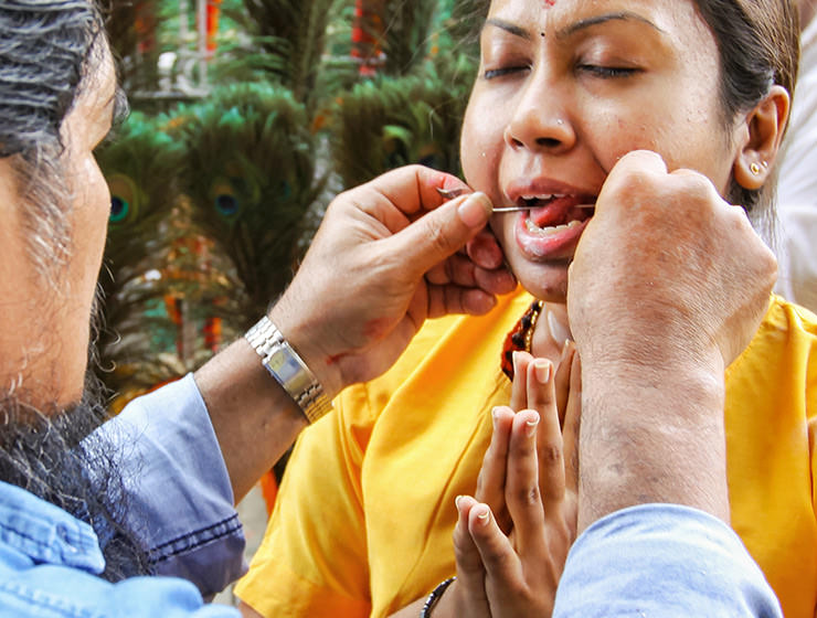 Piercing the tongue of a devotee with a skewer at Thaipusam Festival 2019 at Batu Caves, Malaysia, photo by Ivan Kralj