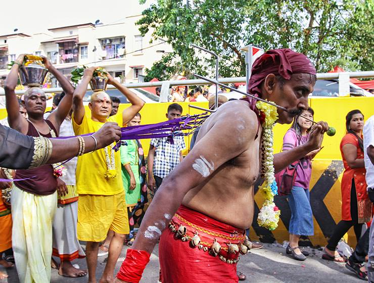 Devotee with pierced cheeks and back skin pulling ropes on the street at Thaipusam Festival 2019 at Batu Caves, Malaysia, photo by Ivan Kralj