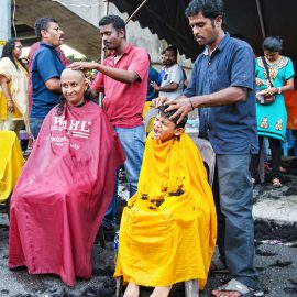 Woman and young boy getting their head shaved in the street at Thaipusam Festival 2019 at Batu Caves, Malaysia, photo by Ivan Kralj