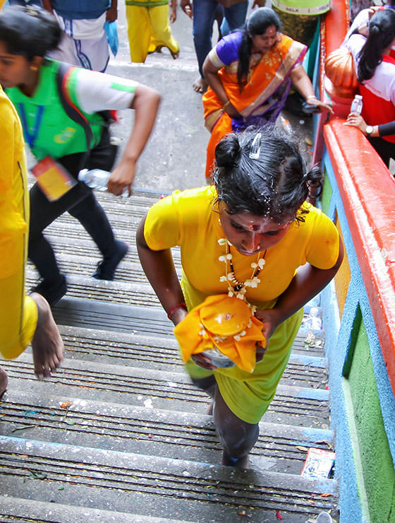 Little girl devotee carrying paal kudam climbing the 272 stairs to Batu Caves, Malaysia, during the Thaipusam Festival 2019, photo by Ivan Kralj