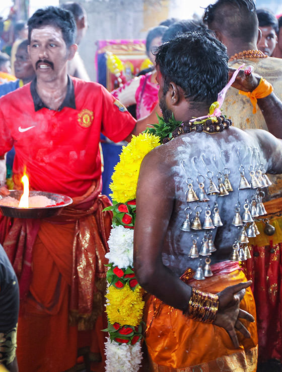 Devotee with bells pierced through the skin of his back at Thaipusam Festival 2019 at Batu Caves, Malaysia, photo by Ivan Kralj