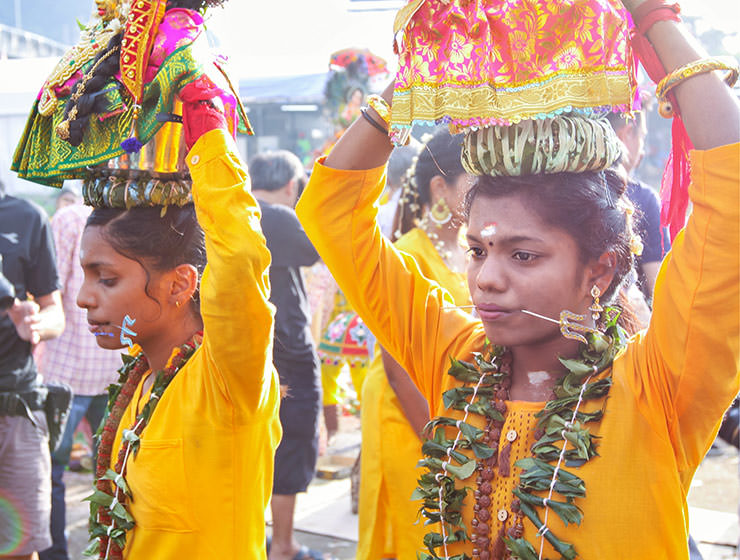 Two female devotees with pierced tongues carrying paal kudam at Thaipusam Festival 2019 at Batu Caves, Malaysia, photo by Ivan Kralj