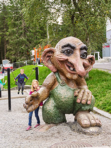 A girl playing around a giant troll sculpture on Mt. Floyen in Bergen, Norway, the wettest place in Europe, photo by Ivan Kralj