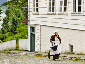 A servant-actress running up the street in the imitation of the 19th-century Bergen at Old Bergen Museum, Norway, photo by Ivan Kralj