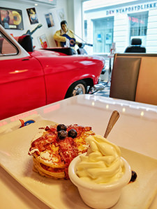 Pancakes with bacon and soft ice-cream served in the retro ambient of Roll & Rock American Diner in Bergen, Norway, with Cadillac and Elvis Presley sculpture in the background, photo by Ivan Kralj