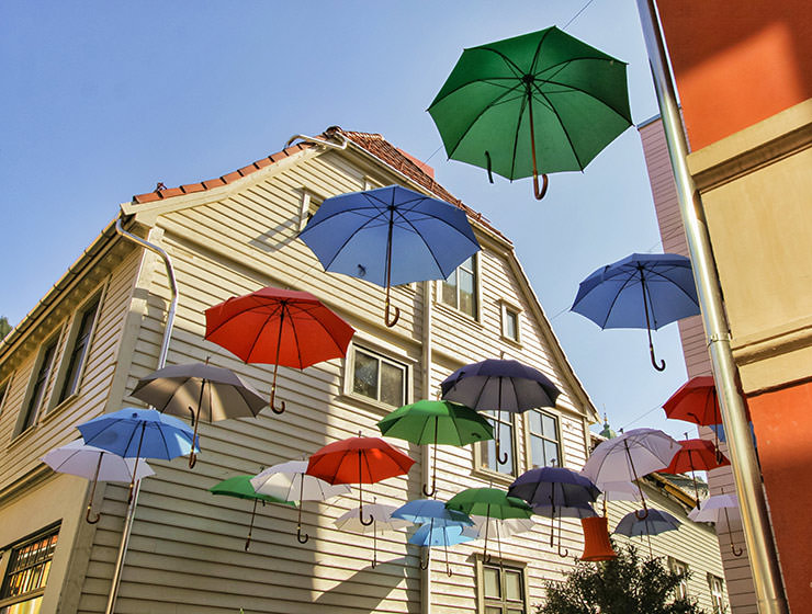 Decorative umbrellas floating in the air above one bar in Bergen, the rainiest city in Europe, photo by Ivan Kralj