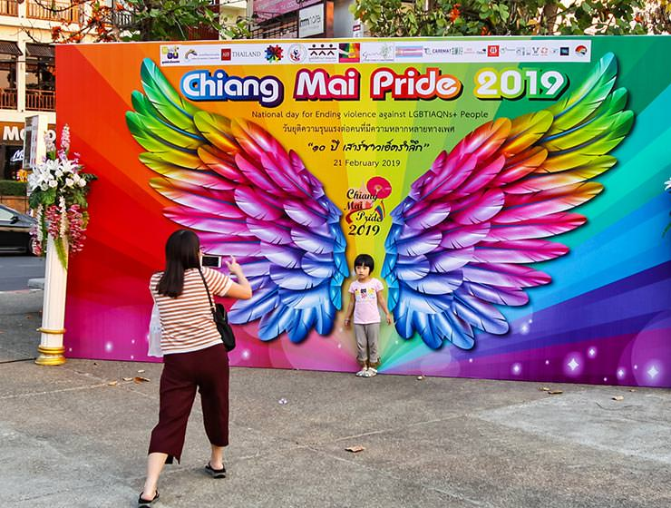 A mother taking a photograph of her child standing in front of the image of rainbow-colored wings at Chiang Mai Pride, gay parade in Chiang Mai, Thailand, photo by Ivan Kralj
