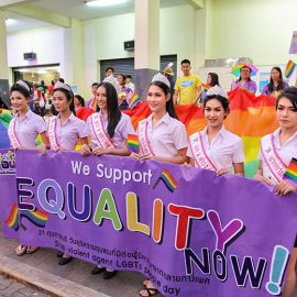 "Crowned ladyboys holding the placard saying ""we support equality now"" in front of the huge rainbow flag at Chiang Mai Pride, gay parade in Chiang Mai, Thailand, photo by Ivan Kralj"