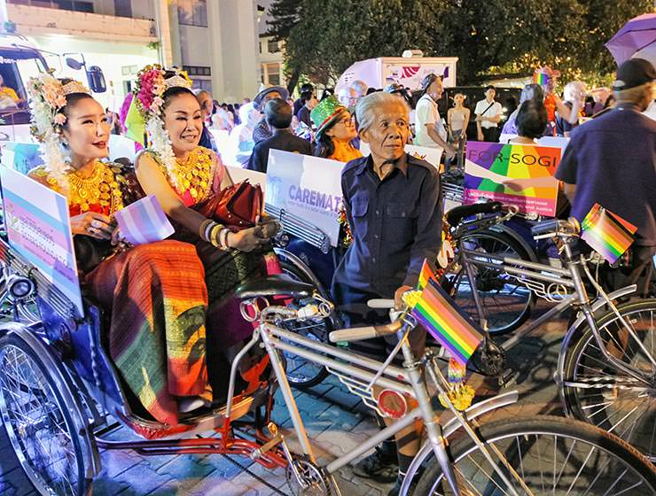 Two ladies sitting in rainbow-adorned the tuk-tuk at Chiang Mai Pride, gay parade in Chiang Mai, Thailand, photo by Ivan Kralj