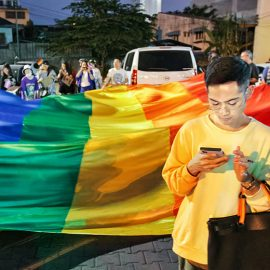 Young man looking at his mobile phone in front of the huge rainbow flag at Chiang Mai Pride, gay parade in Chiang Mai, Thailand, photo by Ivan Kralj