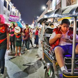 A boy eating his noodles in a tuk-tuk, right next to the Chiang Mai Pride, gay parade in Chiang Mai, Thailand, photo by Ivan Kralj