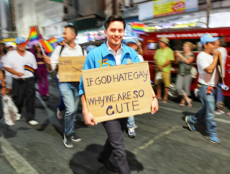 "Participant with placard ""If God hates gays, why are we wo cute"", walking at Chiang Mai Pride, gay parade in Chiang Mai, Thailand, photo by Ivan Kralj"