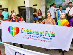 "A priest and other participants with a sign ""Christians at Pride: God loves everyone"", posing at Chiang Mai Pride, gay parade in Chiang Mai, Thailand, photo by Ivan Kralj"