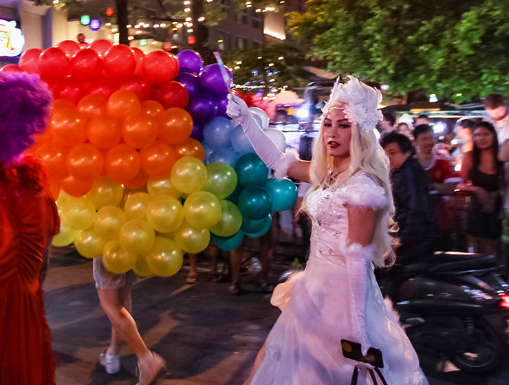 Participant in the white wedding dress in front of the rainbow-colored balloons at Chiang Mai Pride, gay parade in Chiang Mai, Thailand, photo by Ivan Kralj