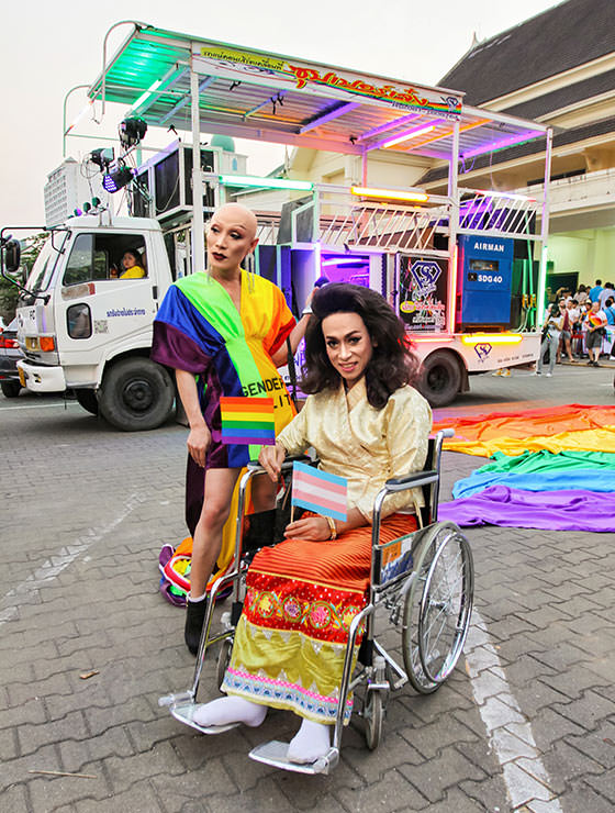 Bold ladyboy in rainbow dress and ladyboy in wheelchair posing at Chiang Mai Pride, gay parade in Chiang Mai, Thailand, photo by Ivan Kralj