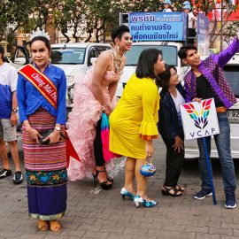 Crowned participant standing while some other participants are taking a selfie in the background at Chiang Mai Pride, gay parade in Chiang Mai, Thailand, photo by Ivan Kralj