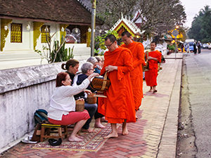 Tourists offer sticky rice to the Buddhist monks passing through the streets of Luang Prabang, Laos, during the alms-giving ceremony or tak bat, photo by Ivan Kralj
