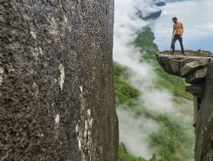 Pipeaway blogger Ivan Kralj standing on the Kalleliklumpen boulder hovering over the cliff in Florli, Lysefjord, one of the best hikes in Norway, photo by Ivan Kralj