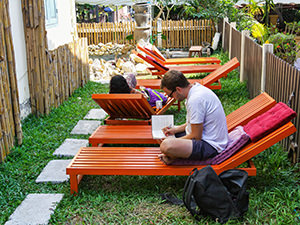 Backpackers resting on the sun loungers in the backyard of the Smile Luang Prabang Hostel, one of the best hostels in Luang Prabang, Laos, photo by Ivan Kralj