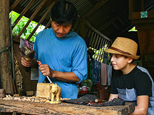 Mr. Lon, the wood carving master, showing the secrets of his trade to a boy attending the Backstreet Academy class session, one of the best things to do in Luang Prabang, Laos, photo by Ivan Kralj