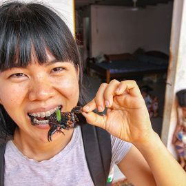 Kim Peou, with braces on her teeth, eating a scorpion at Backstreet Academy's Fear Factor Challenge, in Siem Reap, Cambodia, country where they love to eat insects, photo by Ivan Kralj