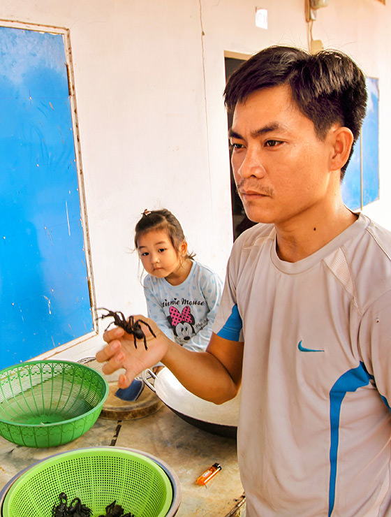 Experience host Ratana Ouch showing the tarantula spider, while his curious 3-year-old daughter lurks what's going on at Backstreet Academy's Fear Factor Challenge cooking class in Siem Reap, Cambodia, a country where they love eating insects, photo by Ivan Kralj