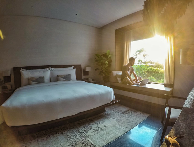 Pipeaway blogger Ivan Kralj sitting on the daybed with bright sun coming through the large window, in the room of Treeline Urban Resort in Siem Reap, Cambodia - what does it take to make it to two years of travel blogging, photo by Ivan Kralj