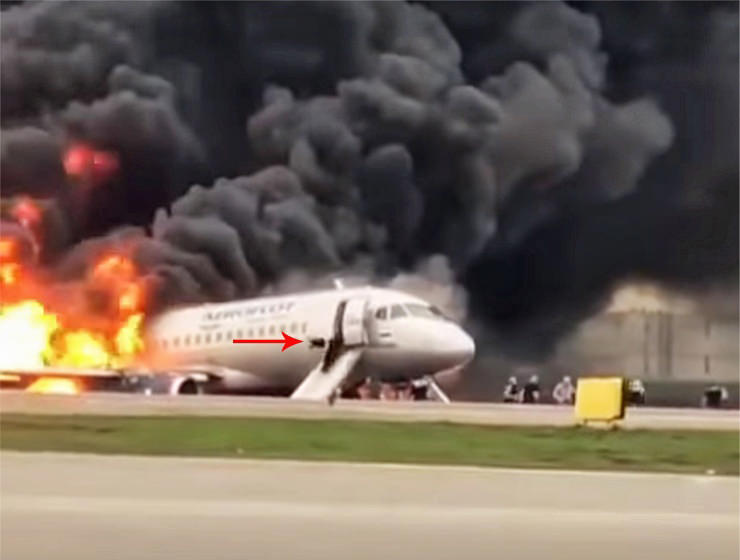 A passenger from an Aeroflot flight crashed in Moscow jumping on an evacuation slide together with carry-on luggage, while flames are swallowing the plane, screenshot from Youtube video - The Aviation Herald