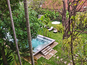 Silver swimming pool behind the lush tropical greenery at Jaya House RiverPark hotel in Siem Reap, Cambodia, photo by Ivan Kralj