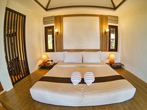 Bed in Mooban Talay Resort beachfront bungalow, with towels wrapped in a from of a seashell, Koh Samet, Thailand, photo by Ivan Kralj
