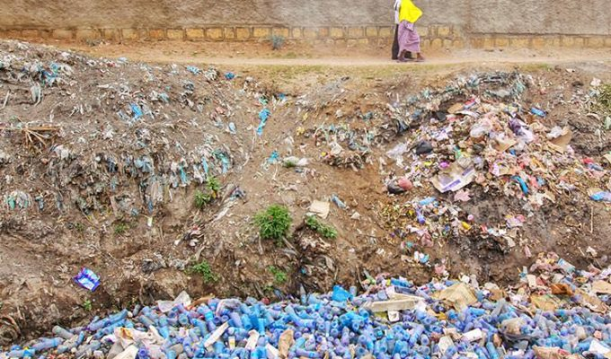 Ethiopian couple walking by the walls of the ancient city of Harar, above the canal filled with plastic bottles and other waste, an example of plastic pollution, photo by Ivan Kralj