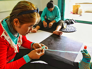 "Hardworking women ""weaving"" the plastic bags into usable objects at Rehash Trash, a social enterprise in Siem Reap, Cambodia, photo by Ivan Kralj"