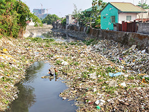 "Two boys looking for ""valuables"" in the garbage-filled river in San Jose district of San Fernando, Pampanga, the Philippines, photo by Ivan Kralj"