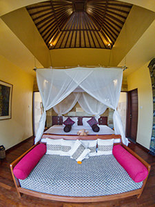 Couch and king size bed under the canopy in the garden suite of Munduk Moding Plantation, nature resort in Bali, Indonesia, photo by Ivan Kralj