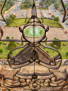 The view of Patuxai park through the Buddha-shaped grille at one of the towers of Patuxai, Vientiane, Laos, photo by Ivan Kralj