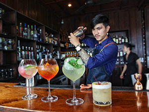 Trying cocktails at The Spirit House is one of the best things to do in Vientiane, Laos; a barman is shaking the best drinking line-up of the house, photo by Ivan Kralj