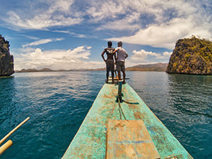 Okoy crew standing on the forecastle of bangka, a boat serving Coron Island Tour in Palawan, Philippines, photo by Ivan Kralj