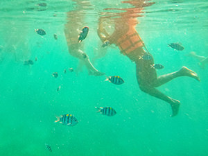 Underwater image of snorkelers in orange life jackets, swimming during the Coron Island Tour in Palawan, the Philippines, photo by Ivan Kralj