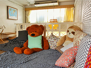 Common lounge room at Pakping Hostel, with pillows and big plush teddy bear and sloth toys, in Chiang Mai, Thailand, photo by Ivan Kralj