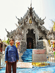 Kru Tu, silversmith artist, standing in front of the Silver Temple she helped decorating, but cannot enter because she is a woman, in Chiang Mai, Thailand, photo by Ivan Kralj