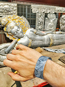 Dragon-decorated aluminum bracelet on the hand, made during the Backstreet Academy workshop in the learning center for the silverware art in Wat Sri Suphan, the Silver Temple of Chiang Mai, Thailand, photo by Ivan Kralj
