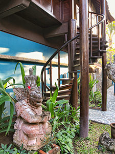 Indonesian sculpture in front of an old Javanese house repurposed as a hotel suite at Tugu Bali, one of Indonesia's best luxury escapes, photo by Ivan Kralj